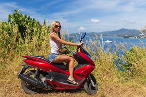 Young slim woman riding motorbike on a sea coast
