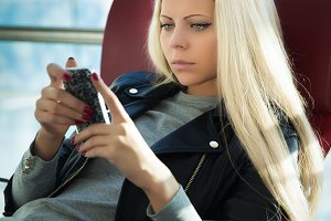 Young pretty blonde woman with mobile phone sitting arport