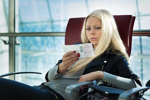 Young pretty blonde woman with air travel tickets sitting