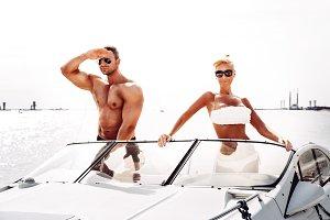 Elegant beautiful couple on boat in a swim wear