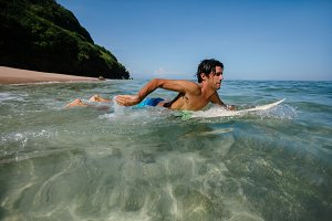 Young man water surfing in ocean