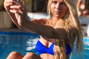 Young pretty blonde woman taking selfie photos swimming pool