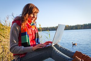 Woman with laptop typing near lake