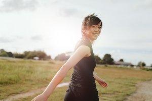 Woman runner walking on field