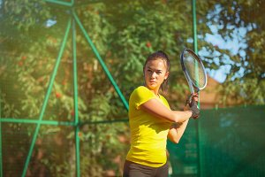 Pretty woman plays tennis outdoors