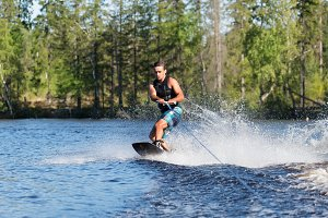Young man riding wakeboard on summer lake