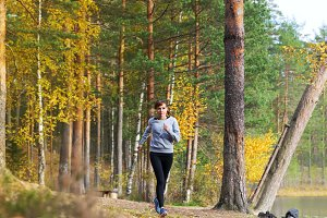 Young woman run in autumn the forest sunset lights
