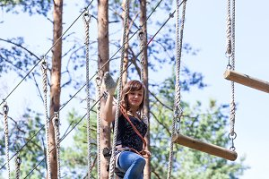 Young brave woman climbing in adventure rope park