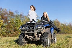 Two elegant women riding extreme quadrocycle ATV