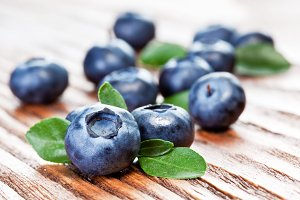 Blueberries with leaves on wooden background.