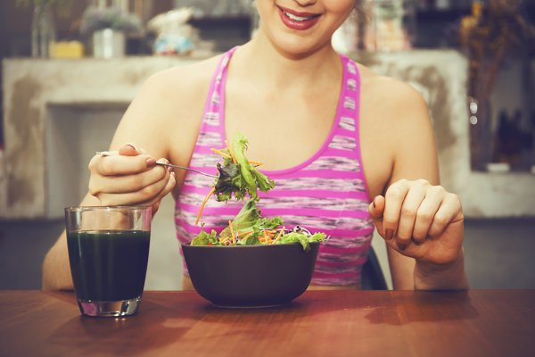 Attractive fitness woman is eating…
