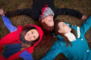 Three young woman lying on an autumn grass