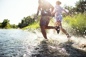 Couple running in shallow water