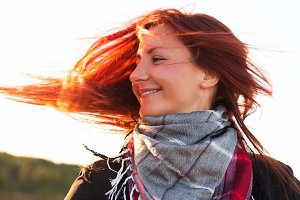 Woman with red hair have fun on the cost in sunlight