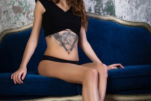 Beautiful young pretty brunette woman with tattoo on sofa