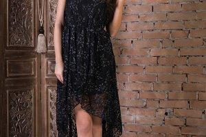 Woman in a black dress on brick wall