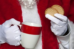 santa claus having coffee with cookies