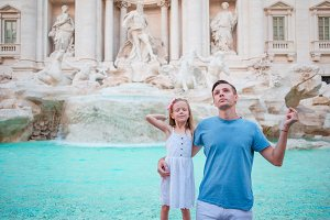 Happy family trowing coins at Trevi Fountain, Rome, Italy for good luck. Little girl and father making a wish to come back.