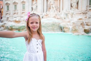 Adorable little girl taking selfie by the Fountain of Trevi in Rome. Happy kid enjoy her european vacation in Italy