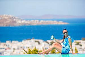 Young woman applying sunscreen on her legs, sitting on the edge of pool background old town Mykonos in Europe