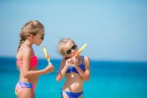 Happy little girls eating ice-cream on the beach.