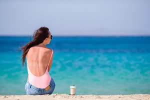 Young beautiful woman on the beach during tropical vacation. Girl drink cold coffee on one of the beautiful beaches in Mykonos, Greece, Europe.