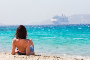 Young girl on the beach background big liner. Woman enjoy her wekeend on one of the beautiful beaches in Mykonos, Greece, Europe.