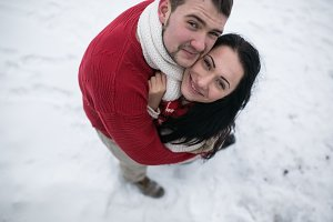 man and woman hugging in snow-covered park