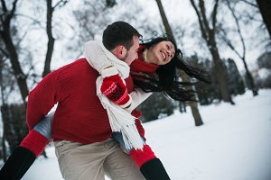 man and woman having fun in the snow-covered park