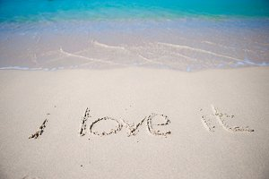 Word i love it handwritten on sandy beach with soft ocean wave on background