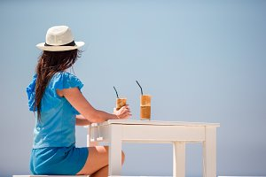 Young girl drinking cold coffee enjoying sea view. Beautiful woman relax during exotic vacation on the beach enjoying frappe