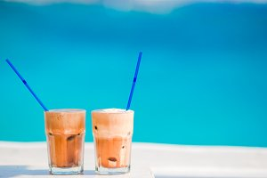 Frappe, ice coffee on the beach. Summer iced coffee frappuccino, frappe or latte in a tall glass background the sea in beach bar