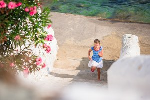 Adorable girl having fun outdoors. Kid at street of typical greek traditional village with white walls and colorful doors on Mykonos Island, in Greece