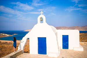 Young woman and traditional white church with sea view in Mykonos island,Greece