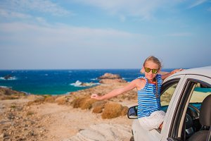Little girl on vacation travel by car background amazing sea view