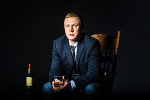 Businessman wearing a jacket with  glass of whiskey sitting on  chair. Bottle alcohol at dark studio background. Concept  choice, privileges, solution problems