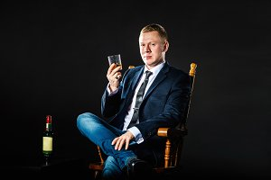 The happy businessman lifts glass of whisky and looks in the camera