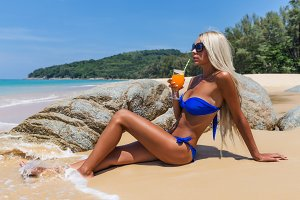 Slim blonde long haired woman bikini orange cocktail tropical beach