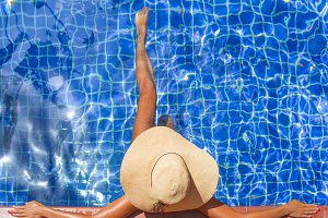 Young slim woman in hat sitting swimming pool