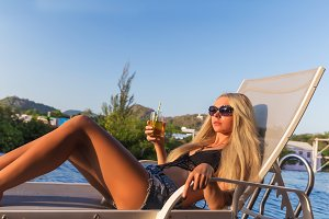 Young slim woman glass juice sunbed near swimming pool