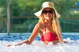 Young pretty blonde woman swimming pool