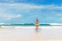 Young pretty woman have sun bath on the cost ocean