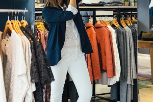 Woman fitting clothes in store