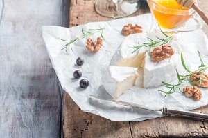 Brie cheese and slice on a wooden board