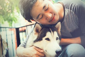 Young Asian male dog owner hugging and embracing the Husky Siberian dog pet with love and care