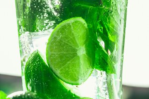 glass of mojito with lime and mint close-up ice cube on a dark background