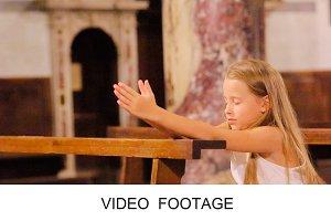 Cute little child praying in church