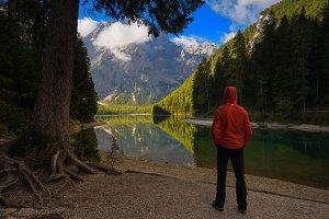 Man looking at Braies lake, Italy