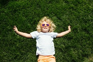 Little blonde girl lying on grass