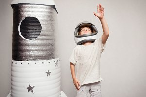 Happy child dressed in an astronaut costume playing with hand ma